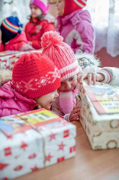 COURTESY OF SAMARITANS PURSE - Children from Romania eagerly peak inside a shoebox during an Operation Christmas Child event during a previous year of the program.