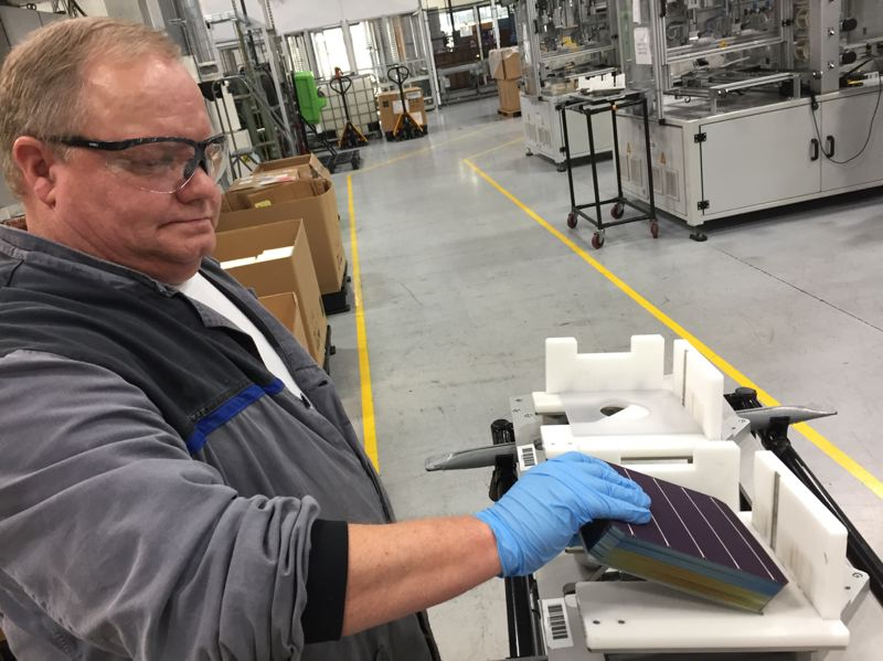 COURTESY OF  CASSANDRA PROFITA, OPB/EARTHFIX - John Clason loads solar cells into a tray to be made into panels at the SolarWorld Americas manufacturing plant  in Hillsboro.