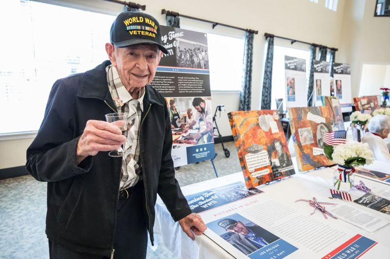 TIMES PHOTO: JONATHAN HOUSE - U.S. Navy veteran Joe Rolison shows off his mixed-media artwork during a reception at Marquis Tualatin Assisted Living.