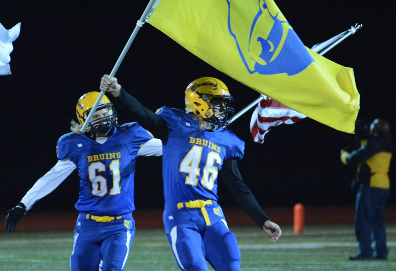 OUTLOOK PHOTO: DAVID BALL - Barlow teammates Brody Carlson, 46, and Devon Turner, 61, carry Bruin flags to midfield before this years rivalry game against Gresham.