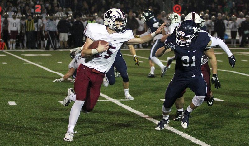 PAMPLIN MEDIA GROUP: MILES VANCE - Sherwood junior running back Ryan Scroggin stiff-arms Lake Oswego's Keenan DeRaeve during the Bowmen's 45-0 loss at Lake Oswego in the second round of the Class 6A state playoffs on Friday.