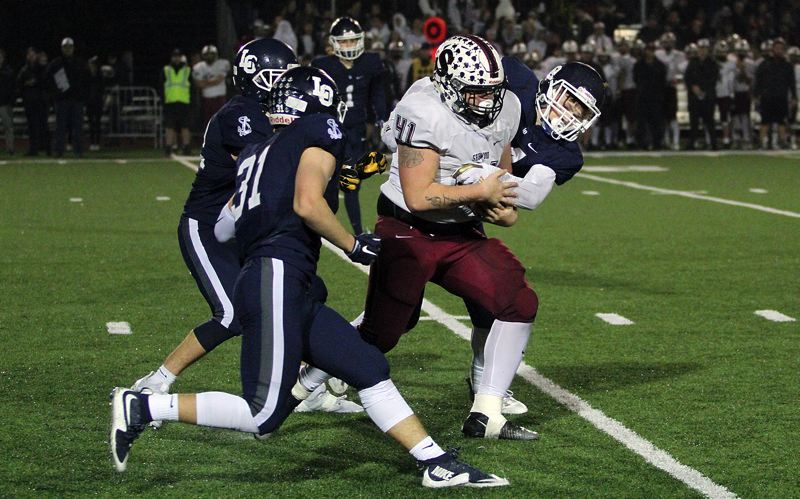 PAMPLIN MEDIA GROUP: MILES VANCE - Sherwood senior tight end end Sterling Goldstein carries Lake Oswego defenders with him after making a catch during his team's 45-0 loss at Lake Oswego High School in the second round of the Class 6A state playoffs on Friday.