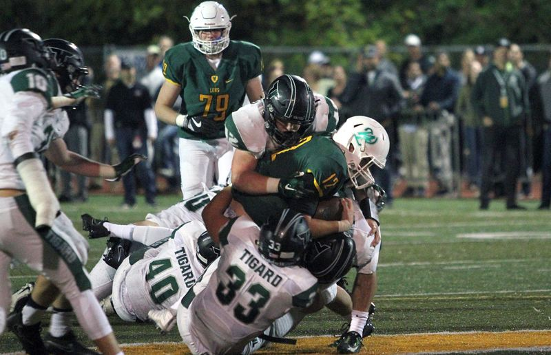 PAMPLIN MEDIA GROUP: MILES VANCE - Tigard defenders, including senior Kyle Bay (33) and junior Carter Dennis bring down West Linn quarterback Ethan Long during the teams' first game this season.
