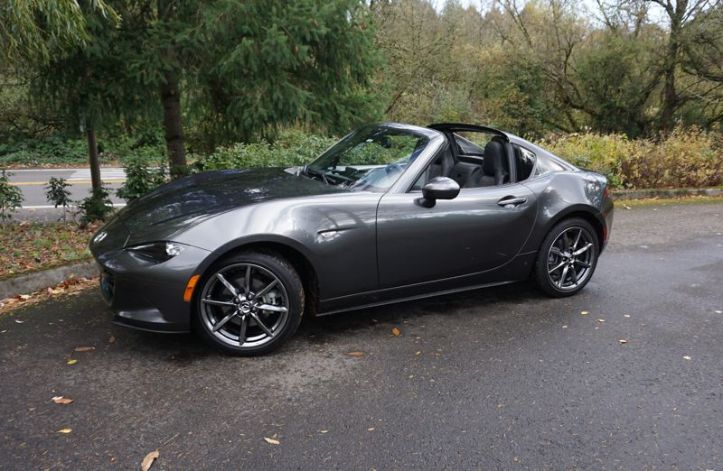 PORTLAND TRIBUNE: JEFF ZURSCHMEIDE - With the 2017 Mazda Miata RF, there is a structure behind the head of the driver that lifts up to fold the roof away, and then comes back down to keep the wind buffeting under control. The result is a Miata that you can use as a cozy and dry hardtop sports car through the Portland winter, but in just twelve seconds you can change it into an enjoyable open sports car.