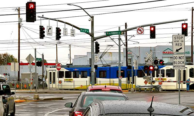 DAVID F. ASHTON - TriMet MAX Orange Line Light Rail trains usually block an intersection only for moments; but Inner Southeast neighbors say freight trains can block the road for an hour.