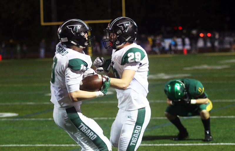 DAN BROOD - Tigard seniors Skylar Holloway (left) and Spencer Smith celebrate following Holloway's game-clinching interception in the Tigers' 24-21 state playoff quarterfinal victory at West Linn on Friday.