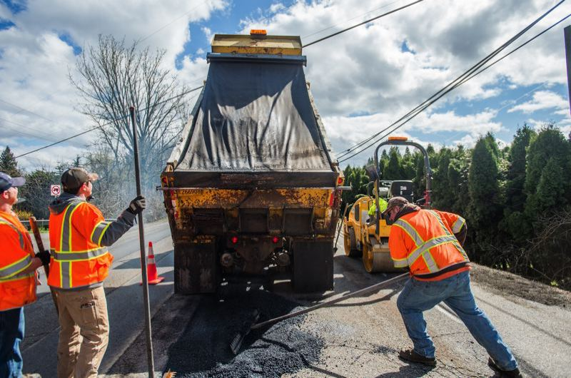 FILE PHOTO - A city of Gresham crew works to repave a road after damage caused from last winter's severe weather.