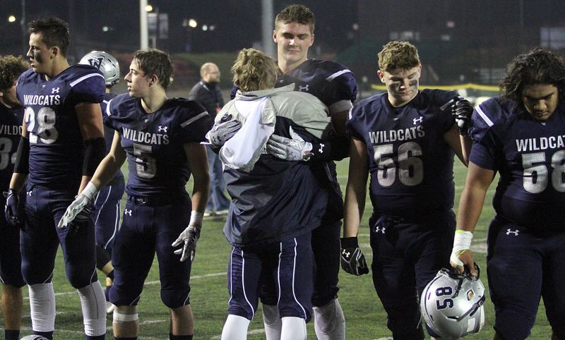 PAMPLIN MEDIA GROUP PHOTO: MILES VANCE - Wilsonville senior Draco Bynum accepts a hug from a teammate at the end of their team's loss in Saturday's Class 5A state semifinals.