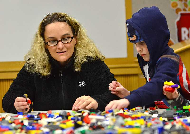 SPOKESMAN PHOTO: VERN UYETAKE - Heather and Jason Kernan sort through the piles of Lego for the right pieces.