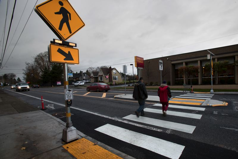 TIMES PHOTO: JAIME VALDEZ - Pedestrians in Tigard cross Hall Boulevard toward Wells Fargo using a just-upgraded crosswalk.