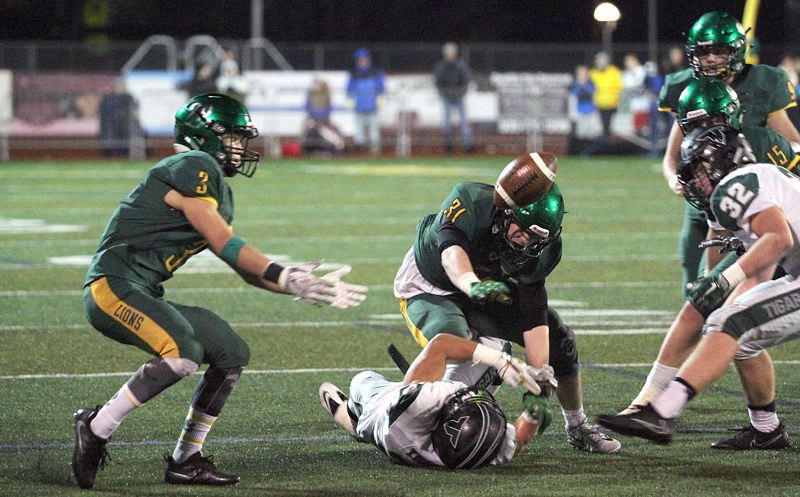 TIDINGS PHOTO: MILES VANCE - The West Linn defense kept hitting until the final whistle this year — here, Zack Huffstutter (center) forces a Tigard fumble that Cody Fretwell recovered at the end of  Friday's Class 6A state quarterfinal.