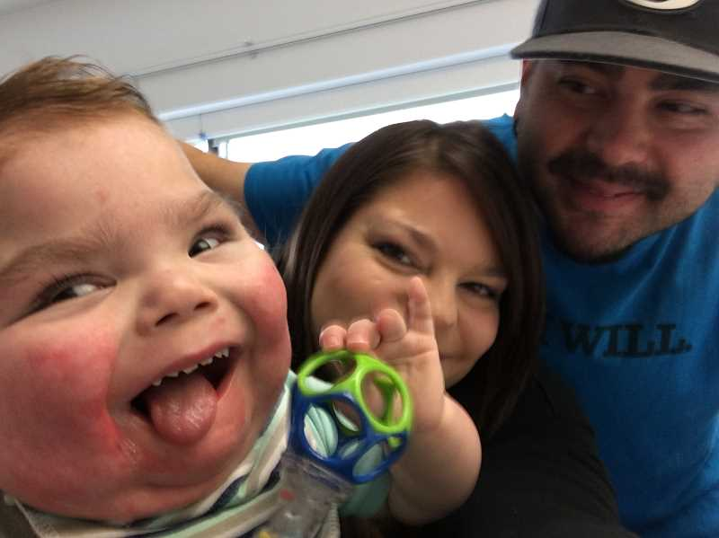 COURTESY OF TARA OUELLETTE-STONE - Ashton Stone mugs for the camera shortly before arriving back in Portland and his Beaverton home as parents Tara Ouellette-Stone and Michael Stone look on.
