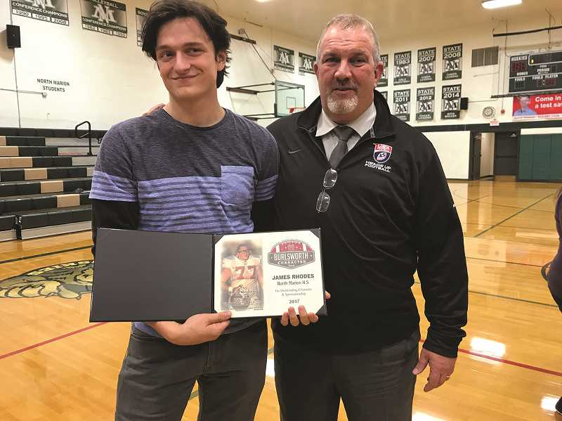 COURTESY PHOTO - North Marion senior James Rhodes presents his Brandon Burlsworth Character Award along with football Head Coach Doug Bilodeau. The Burlsworth award is a national honor that recognizes players who show strength of character and morals both on and off the field.