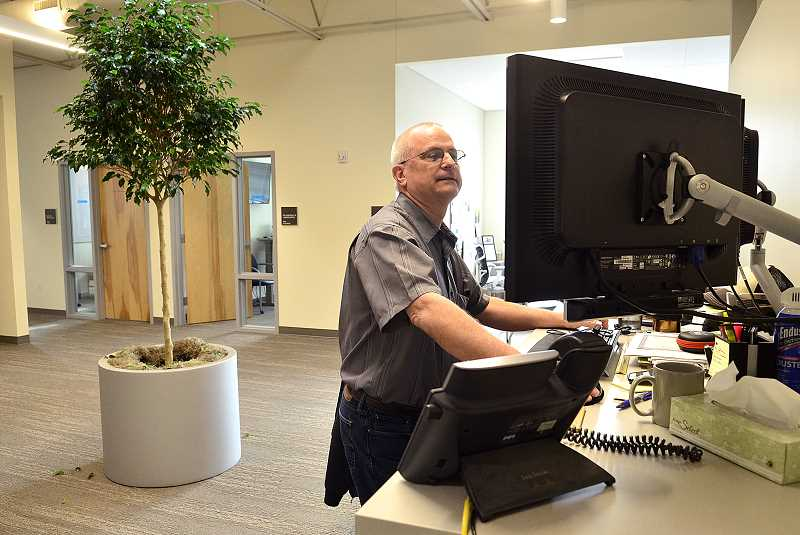 REVIEW PHOTO: VERN UYETAKE - Mike Beard works at a standing desk in the Operations and Maintenance Center's new central area, where most of the Public Works offices are located.