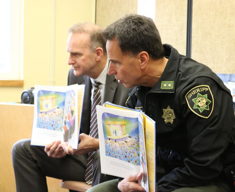 OUTLOOK PHOTO: ZANE SPARLING - Rod Underhill and Mike Reese display pages from the picture book 'Officer Buckle and Gloria' on Friday, Nov. 17, at Covenant Presbyterian Church, 18630 S.E. Division Street.