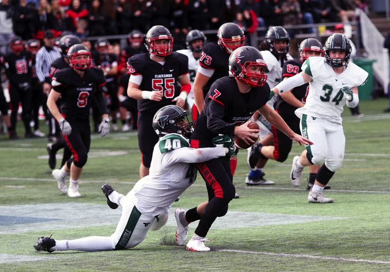 DAN BROOD - Tigard junior defensive end Noah Jackman (40) drags down Clackamas quarterback Mitchell Modjeski for a sack during Friday's state playoff semifinal game.