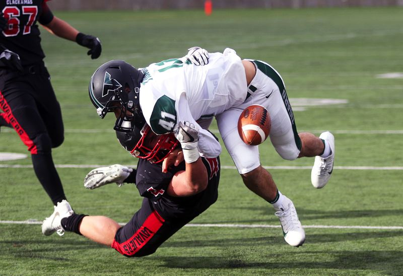 DAN BROOD - Tigard freshman quarterback Drew Carter loses the ball, which bounced out of bounds, as he's tackled by Clackamas junior Jake Bushman in Friday's state playoff semifinal game.