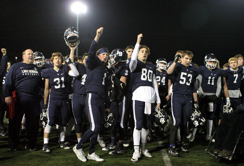 REVIEW PHOTO: MILES VANCE - Lake Oswego's Andrew Ramey (No. 1) and Justin Peeler (No. 80) signal to the Laker crowd at the end of their team's 49-27 loss to South Medford in the Class 6A state semifinals at Hillsboro Stadium on Friday.