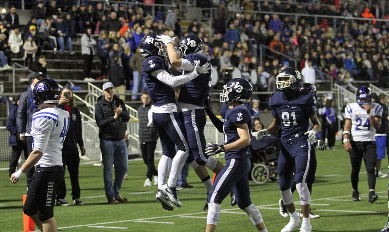REVIEW PHOTO: MILES VANCE - Lake Oswego's Casey Filkins (center, left) accepts congratulations after scoring his team's first touchdown during its 49-27 loss to South Medford in the Class 6A state semifinals at Hillsboro Stadium on Friday.