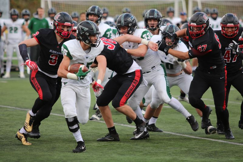 REVIEW/NEWS PHOTO: JIM BESEDA - Tigard's Braden Lenzy (25) looks for running room as Clackamas' Jakobe Erskine (3), Perry Crossgriffe (36) and Kelsen Hennessy (67) close in from all sides during Friday's semifinal.