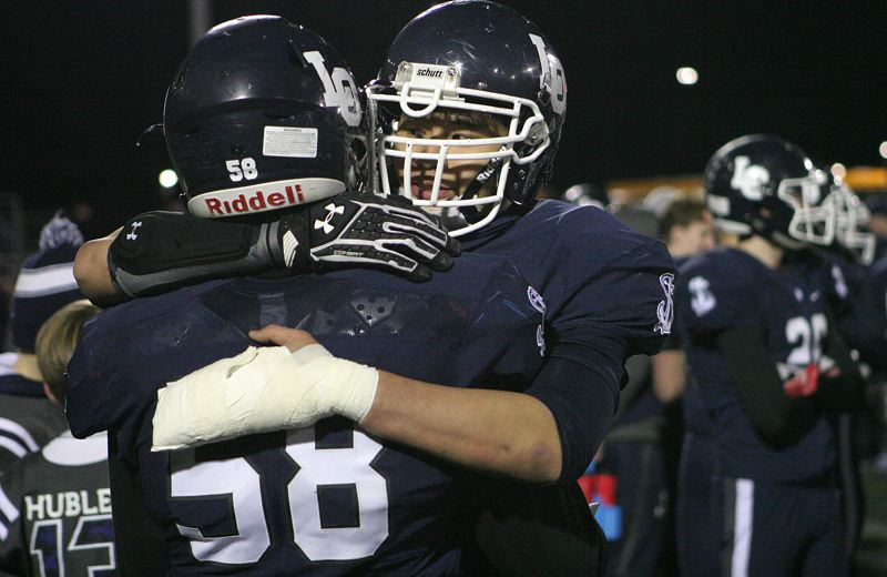REVIEW PHOTO: MILES VANCE - Lake Oswego's Mario Pronnorongvat (right) hugs teammate Mike Mercep at the end of their team's 49-27 loss to South Medford in the Class 6A state semifinals at Hillsboro Stadium on Friday.