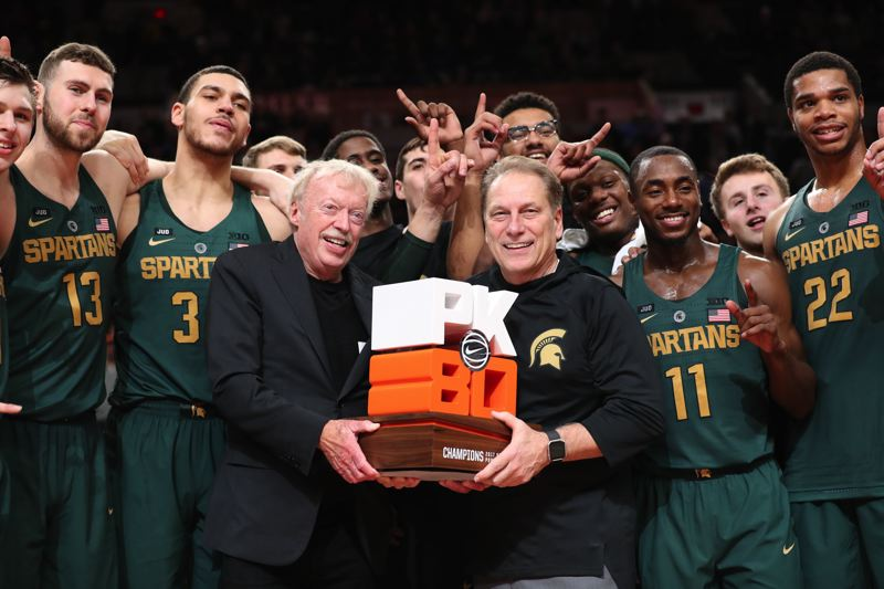 TRIBUNE PHOTO: JAIME VALDEZ - The Michigan State men's basketball team celebrates with Nike co-founder Phil Knight after claiming first place in the PK80 Invitational Victory Bracket with a finals victory over North Carolina on Sunday at Moda Center.