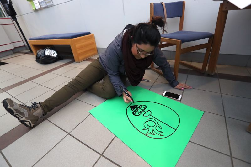 FILE - Yanely Rivas draws a poster at Tigard City Hall before a council meeting in April at which activists called for Tigard to declare itself a 'sanctuary city.'