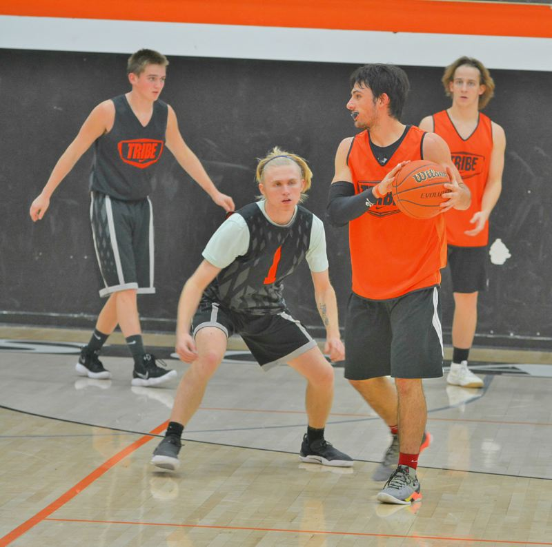 SPOTLIGHT PHOTO: JAKE MCNEAL - Joey Wagenknecht (1) checks Chris Bendle as Bradley Verbout, back left, defends against Ian Johnson, back right, at practice Monday, Nov. 20, at Scappoose High School.