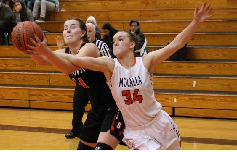 PIONEER PHOTO: CONNER WILLIAMS - Molalla senior Alicia Schultz (34) fights for possession with Kaylie Kopra during the Indians' 56-42 win over Scappoose last season. Schultz will again be one of Molalla's biggest weapons on both sides of the ball this year.