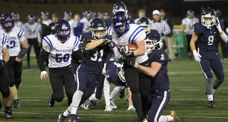 REVIEW PHOTO: MILES VANCE - Lake Oswego's Keenan DeRaeve (No. 31) and Sam Haney team up to tackle South Medford's Trent Snyder during their team's semifinal loss on Friday at Hillsboro Stadium.