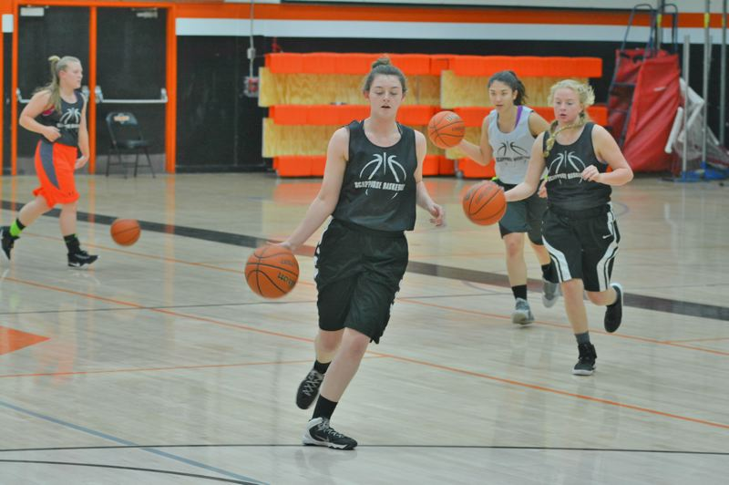 SPOTLIGHT PHOTO: JAKE MCNEAL - Shaylan Smith, center, dribbles through a crossover drill in practice Tuesday, Nov. 21.
