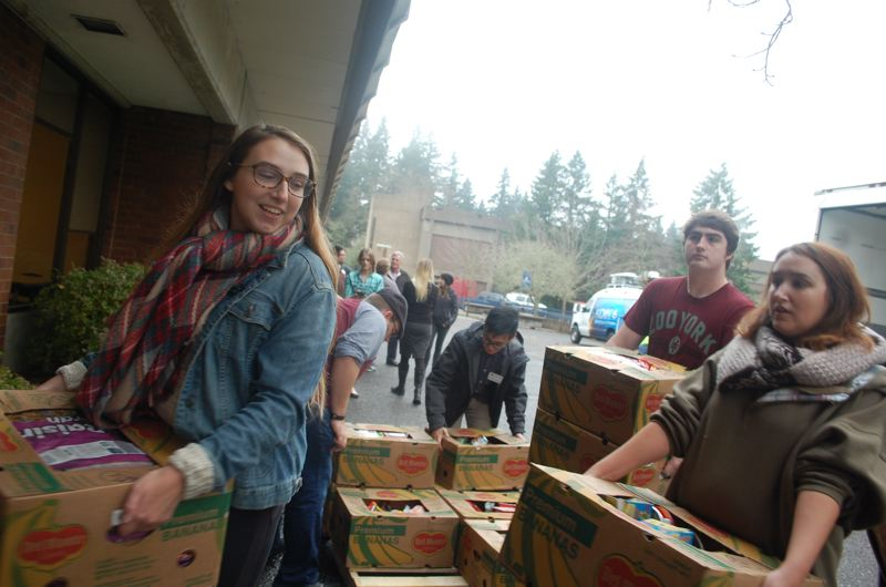 PHOTO BY: RAYMOND RENDLEMAN - Tori (left) and Kristin Woods helped stock the student pantry at Clackamas Community College with the help of their dad and Safeway on Nov. 21.