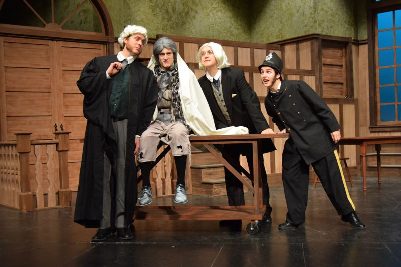 PHOTO BY KARMIN TOMLINSON  - Dennis Kelly as Solomon Rothschild discusses a point of law with Jaedon Lewis as Jacob Marley, Taryn McGhee as Ebenezer Scrooge and Ryan Takko as the Bailiff.