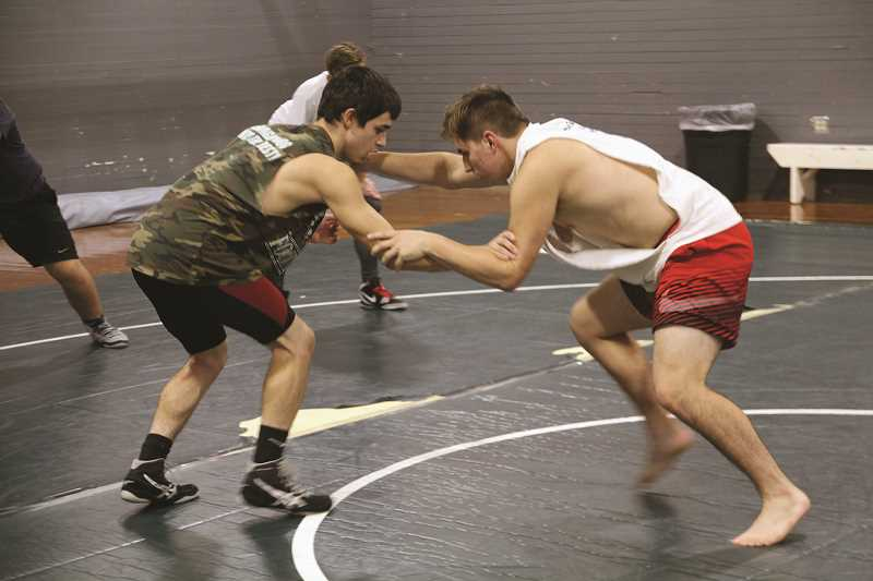 LINDSAY KEEFER - Nick Perez and Bryce Vandervort spar against each other as the Trojans prepare for their season opening tournament in Harrisburg on Friday.