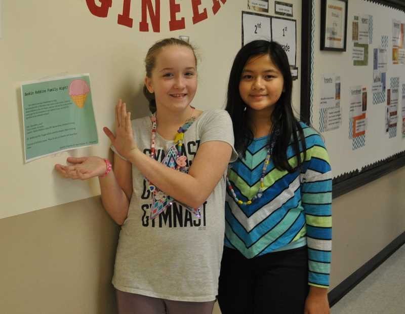 TIMES PHOTO: BLAIR STENVICK - Dakota Wright and Angelina Pham pose next to a flier they created for a fundraiser benefitting homeless students at Elmonica Elementary School.