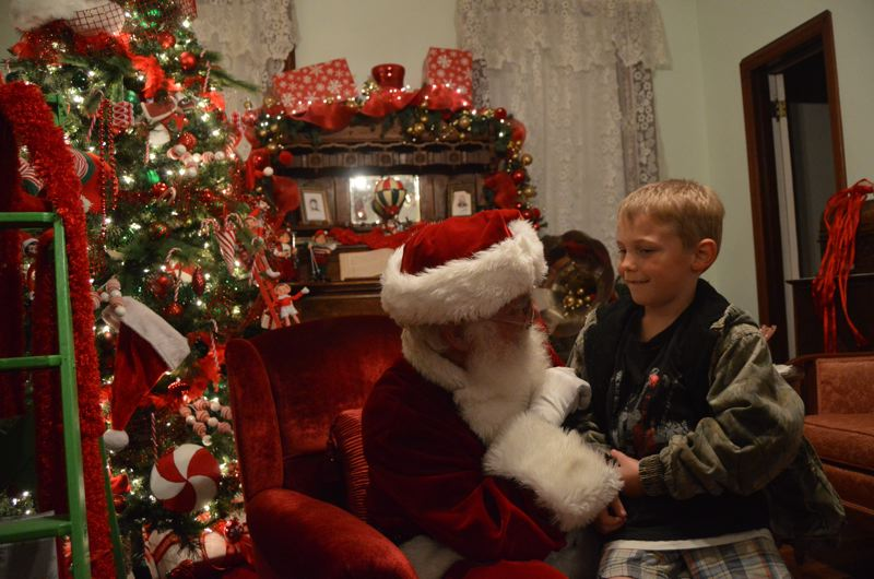 SPOTLIGHT PHOTO: COURTNEY VAUGHN - Santa Claus visits the Watts House Pioneer Museum in Scappoose Monday evening, Nov. 27. Children visited with Santa, giving their wishlists and leaving with candy canes.