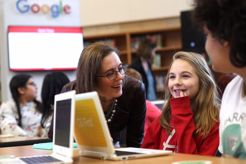 TRIBUNE PHOTO: JAIME VALDEZ - Oregon Governor Kate Brown talks with a Parkrose Middle School student during a Tuesday Nov. 28 computer science lesson in the Google CS First Roadshow.