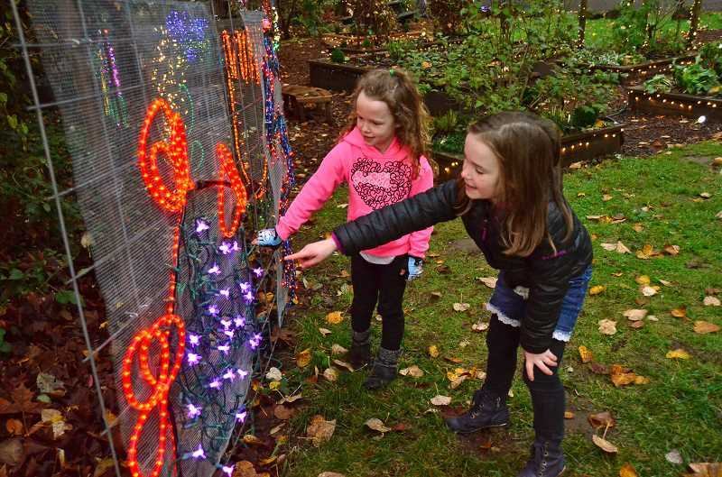 TIDINGS PHOTOS: VERN UYETAKE - Marlowe, left, and Finley Springer of West Linn check out some of the light displays at Maddax Woods.