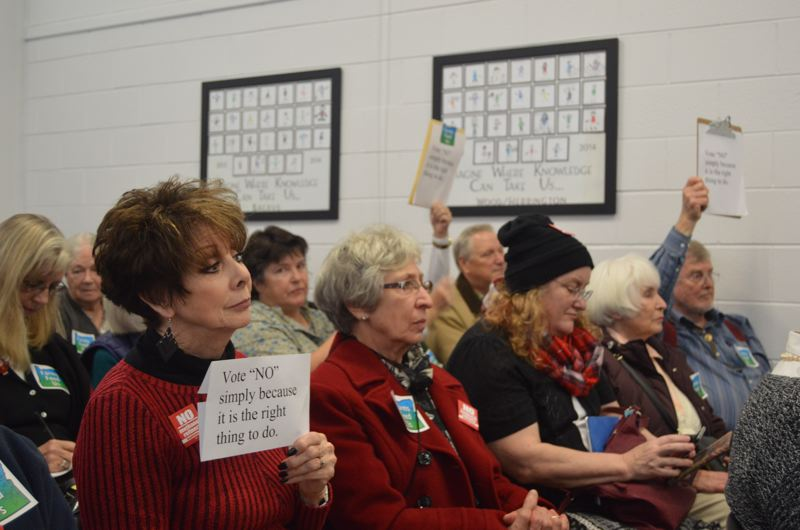 SPOTLIGHT PHOTO: COURTNEY VAUGHN - Members of the public hold up signs urging Columbia County commissioners to 'vote no simply because it is the right thing to do,' Wednesday, Nov. 29 during deliberations on a proposed Port Westward Industiral Park expansion. The project was approved.