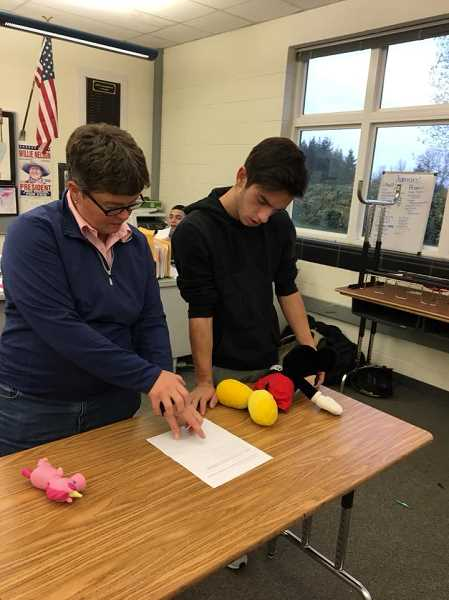 SUBMITTED PHOTO - Dr. Jennifer Swanson helps Josh Kropf in preparation for the state veterinary event Nov. 18-19.