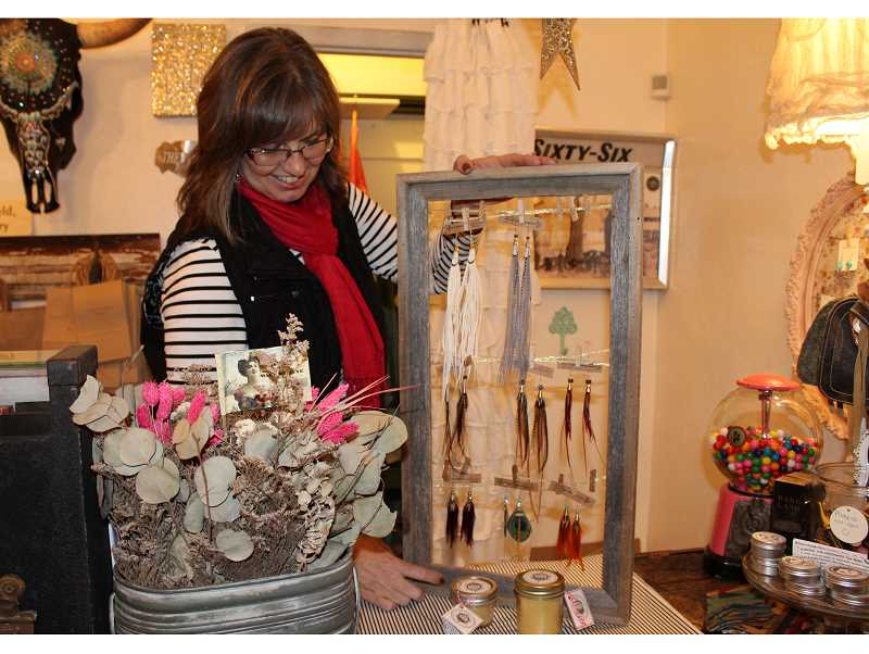 HOLLY M. GILL - Teresa Leno displays some of the locally made earrings and balms at the White Buffalo Boutique on Southwest Fifth Street, in Madras.