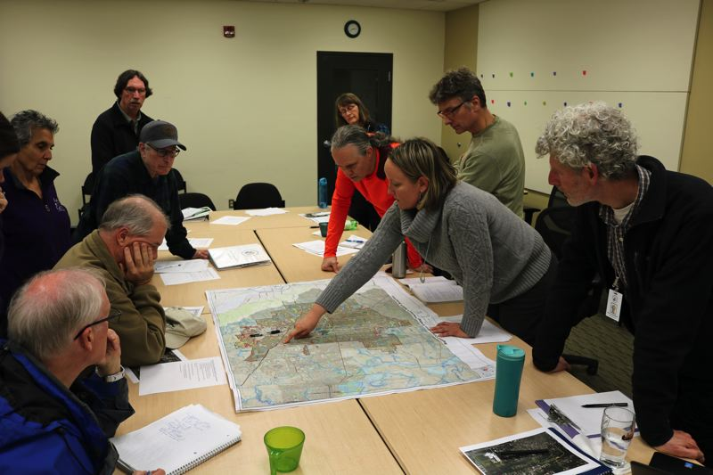 STAFF PHOTO: BRIANA BAYER - Committee member pour over a map of the park district in discussing best strategy for natural resource land acquisition.