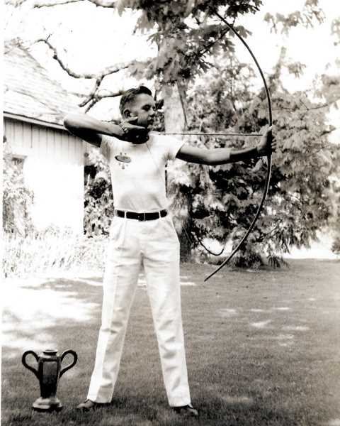 COURTESY PHOTO - A teenage Robert Nixon shooting his long bow in 1943 with his state championship trophy at his feet.