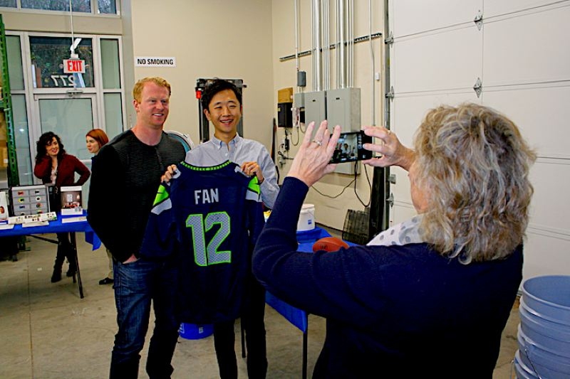 OUTLOOK PHOTO: STEVEN BROWN - Lynn Snodgrass, right, CEO of the Gresham Chamber of Commerce, takes a photo of Seattle Seahawk punter Jon Ryan and  Justin Hwang of Joy Teriyaki.