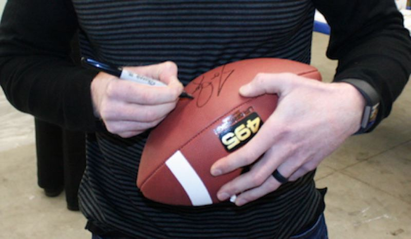 OUTLOOK PHOTO: STEVEN BROWN - Seattle Seahawks punter Jon Ryan signs a football during a meet-and-greet event at Sherwin Williams. Ryan is part of the ownership group of the Gresham GreyWolves baseball team.