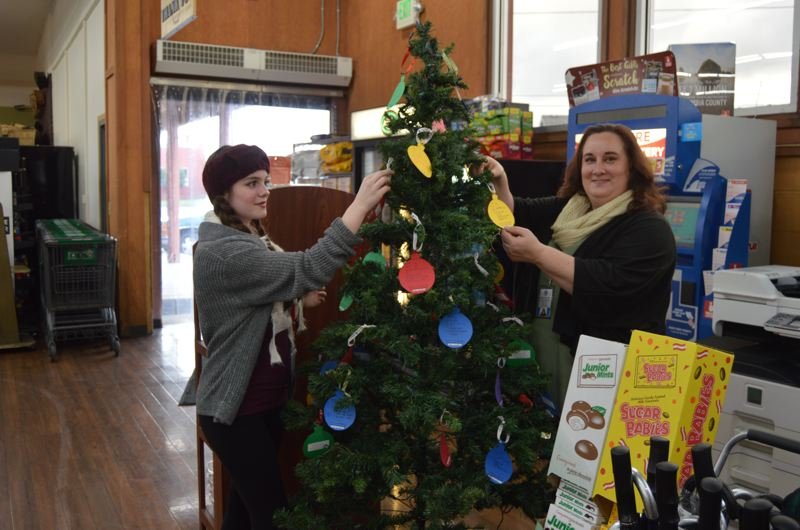 SPOTLIGHT PHOTO: COURTNEY VAUGHN - Andrea Kotkins and Melissa Scath, both with the Child Welfare division of the Department of Human Services, place ornaments on a giving tree at St. Helens Market Fresh. The giving tree lists children in foster care and their holiday wishlists. The tree will stay up through Dec. 11.