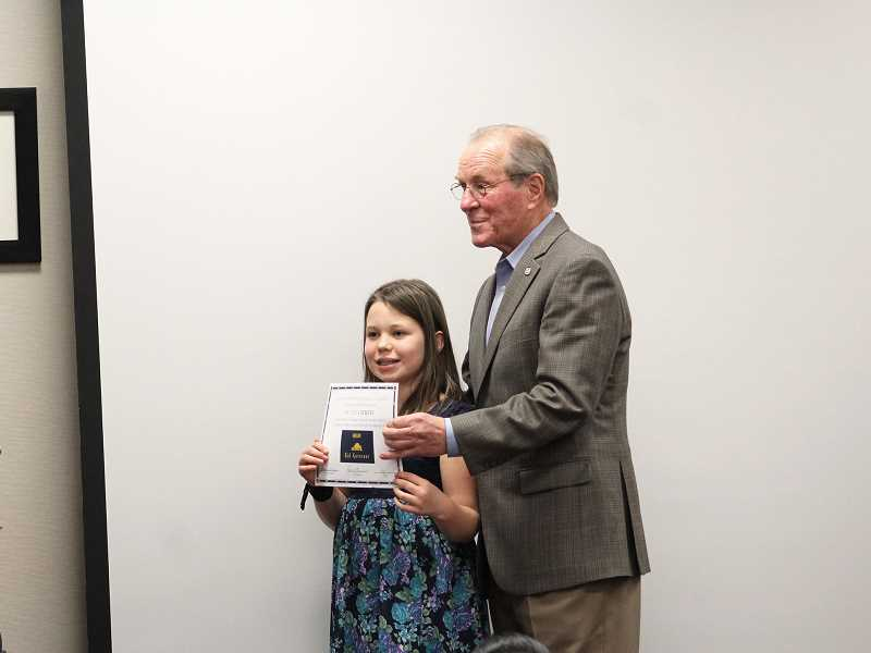 HERALD PHOTO: KRISTEN WOHLERS - Ted Kulongoski presents a certificate to India Stults, who ran for kid governor.