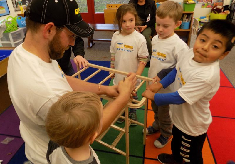 CONTRIBUTED PHOTO: HOLLYDALE ELEMENTARY SCHOOL - Cereghino puts together a rack that will hold some of the new school supplies for Heidi Craddock's kindergarten class.