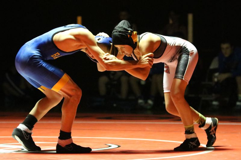 REVIEW/NEWS PHOTO: JIM BESEDA - Oregon City's Emma Baertlein (right) won her high school wrestling debut with a second-round fall over Barlow's Dylan Walsh in Thursday's Mt. Hood Conference dual at Oregon City High.