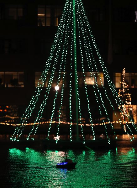 TIMES PHOTO: JAIME VALDEZ - A remote-control boat glides across the Lake of the Commons in front of Tualatin's holiday tree of lights on Friday night.